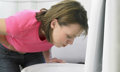 Woman vomiting into toilet