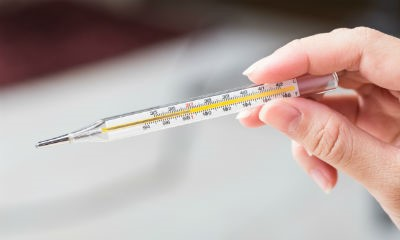 Person measuring temperature with a thermometer